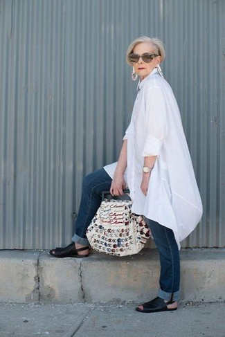 Comment porter: tunique en lin blanche, jean bleu marine, sandales plates en cuir noires, sac fourre-tout en toile brodé blanc