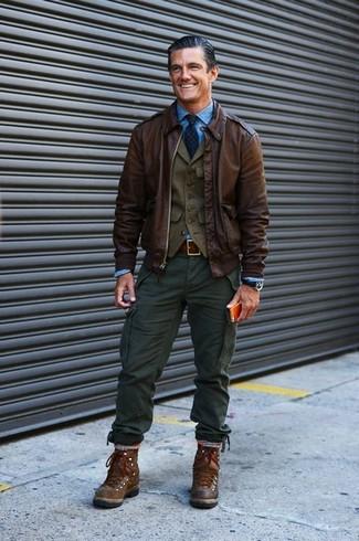 Comment porter: veste à col et boutons en cuir marron foncé, gilet olive, chemise à manches longues bleue, pantalon cargo vert foncé