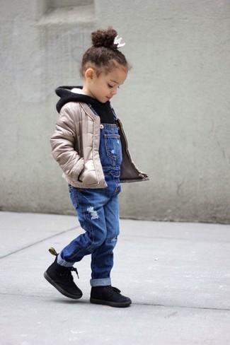 Comment porter: veste matelassée beige, sweat à capuche noir, salopette en denim bleue, bottes noires