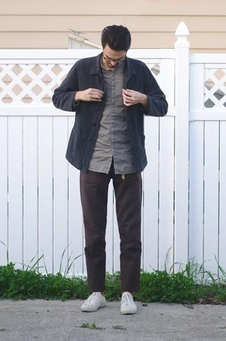 Comment porter une veste-chemise bleu marine: Une veste-chemise bleu marine et un pantalon chino marron foncé sont un choix de tenue idéale à avoir dans ton arsenal. Tu veux y aller doucement avec les chaussures? Termine ce look avec une paire de des baskets basses en toile blanches pour la journée.