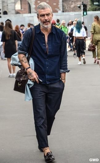 Comment porter une besace en cuir marron foncé: Pour une tenue aussi confortable que ton canapé, pense à porter une veste-chemise bleu clair et une besace en cuir marron foncé. Une paire de des mocassins à pampilles en cuir noirs apportera une esthétique classique à l'ensemble.