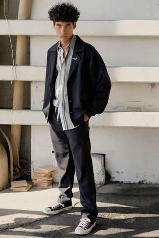 Comment porter un pantalon chino gris foncé: Associe une veste-chemise noire avec un pantalon chino gris foncé pour créer un look chic et décontracté. Si tu veux éviter un look trop formel, assortis cette tenue avec une paire de baskets basses en toile noires et blanches.