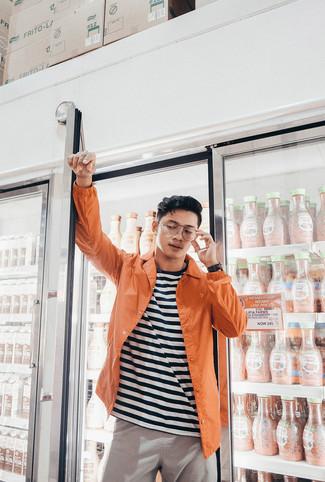 Comment porter: veste-chemise orange, t-shirt à col rond à rayures horizontales blanc et noir, pantalon chino gris, montre en cuir noire