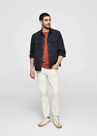 Comment porter: veste-chemise noire, pull à col rond orange, t-shirt à col rond beige, pantalon chino blanc