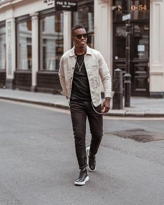 Comment porter un t-shirt à col rond noir: Pense à associer un t-shirt à col rond noir avec un jean noir pour obtenir un look relax mais stylé. Assortis ce look avec une paire de des baskets basses en cuir noires et blanches.