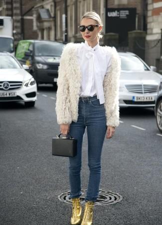 Comment porter: veste de fourrure blanche, chemisier boutonné blanc, jean skinny bleu marine, bottines à lacets en cuir dorées