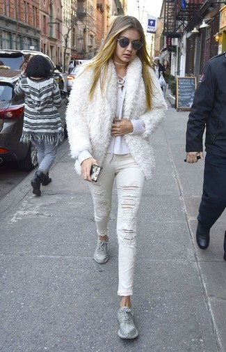 Comment porter un jean skinny déchiré blanc: Pour créer une tenue idéale pour un déjeuner entre amis le week-end, opte pour une veste de fourrure blanche avec un jean skinny déchiré blanc. Jouez la carte décontractée pour les chaussures et choisis une paire de des chaussures de sport argentées.