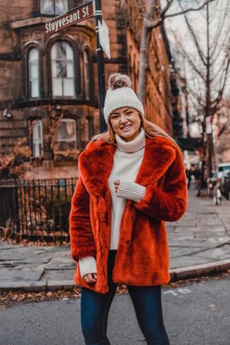 Comment porter: veste de fourrure rouge, pull à col roulé en tricot beige, jean skinny bleu marine, bonnet en tricot blanc