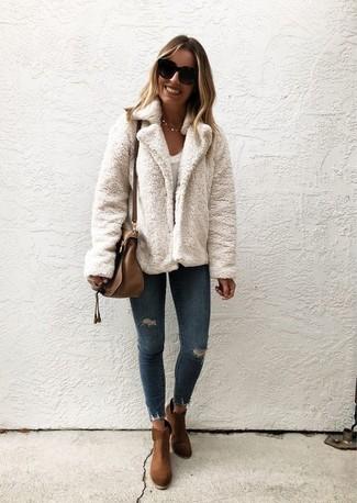 Comment porter: veste de fourrure blanche, t-shirt à col rond blanc, jean skinny déchiré bleu marine, bottines en daim marron