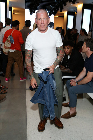 Tenue de Nick Wooster: Veste en jean bleue, T-shirt à col rond blanc, Pantalon chino olive, Chaussures richelieu en cuir marron