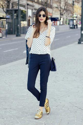 Comment porter: veste en jean bleue, chemisier à manches courtes á pois blanc et noir, pantalon slim bleu marine, baskets basses en cuir dorées