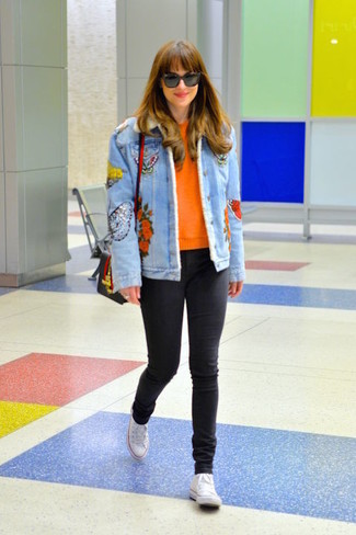 Comment porter: veste en jean brodée bleu clair, pull à col rond orange, jean skinny noir, baskets montantes en toile blanches