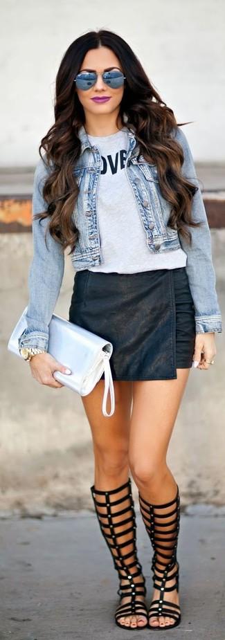 Comment porter: veste en jean bleu clair, pull à col rond imprimé gris, minijupe en cuir noire, sandales spartiates hautes en cuir noires
