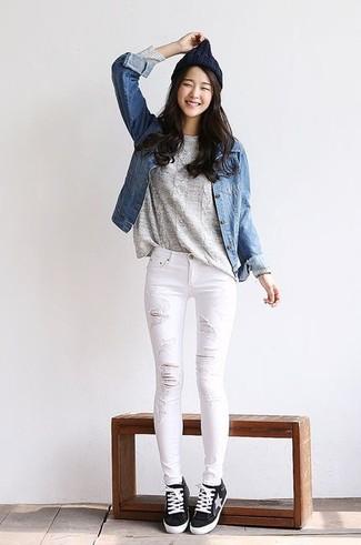 Comment porter: veste en jean bleue, pull torsadé gris, jean skinny déchiré blanc, baskets basses noires et blanches