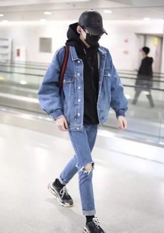 Comment porter: veste en jean bleue, sweat à capuche noir, jean déchiré bleu, chaussures de sport noires