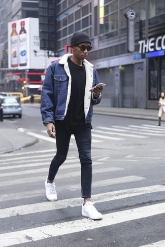 Comment porter: veste en jean bleue, sweat-shirt noir, jean skinny bleu marine, baskets basses en cuir blanches