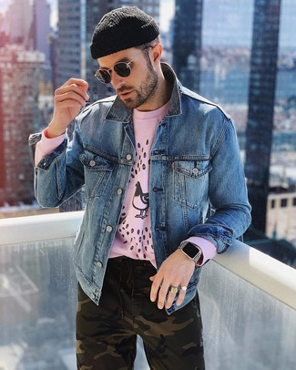 Comment porter: veste en jean bleue, sweat-shirt imprimé rose, pantalon chino camouflage olive, bonnet noir
