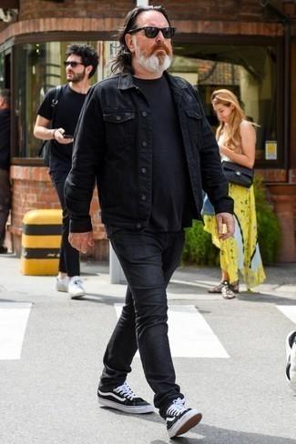 Comment porter des baskets basses en toile noires et blanches: Essaie d'harmoniser une veste en jean noire avec un jean noir pour obtenir un look relax mais stylé. Assortis ce look avec une paire de des baskets basses en toile noires et blanches.