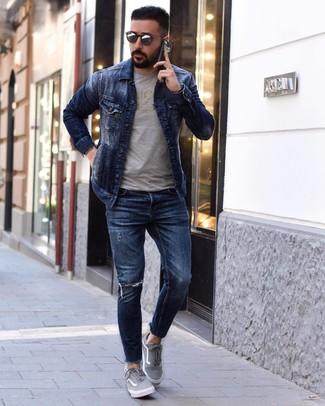 Comment porter: veste en jean bleu marine, t-shirt à col rond imprimé gris, jean skinny déchiré bleu marine, baskets basses en toile grises