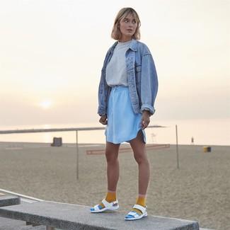 Comment porter: veste en jean bleu clair, t-shirt à col rond gris, minijupe bleu clair, sandales plates en cuir blanches