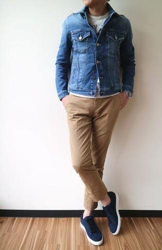 Comment porter: veste en jean bleue, t-shirt à col rond imprimé gris, pantalon chino marron clair, baskets basses en toile bleu marine