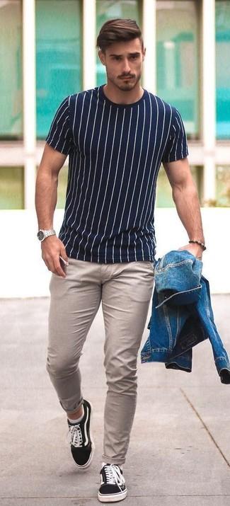 Comment porter: veste en jean bleue, t-shirt à col rond à rayures verticales blanc et bleu marine, pantalon chino beige, baskets basses en toile noires