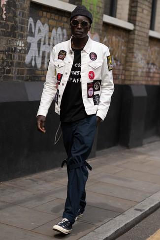Comment porter: veste en jean brodée blanche, t-shirt à col rond imprimé noir et blanc, pantalon chino bleu marine, baskets basses en toile noires