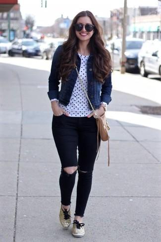 Comment porter: veste en jean bleu marine, t-shirt à manche longue á pois blanc et noir, jean skinny déchiré noir, baskets basses dorées