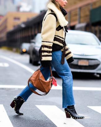 Comment porter: veste en peau de mouton retournée beige, jean bleu, bottines en cuir à clous noires, sac fourre-tout en cuir tabac