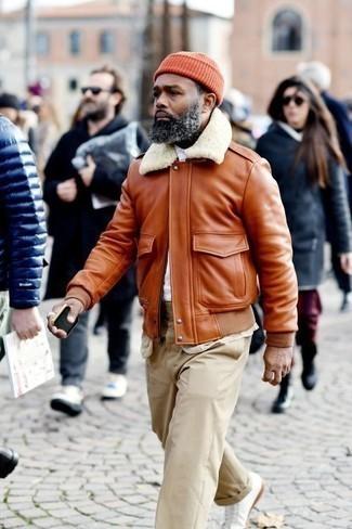 Comment porter une veste en peau de mouton retournée tabac en hiver: Pense à harmoniser une veste en peau de mouton retournée tabac avec un pantalon chino beige pour affronter sans effort les défis que la journée te réserve. Mélange les styles en portant une paire de des baskets basses en cuir blanches. C'est un look que pourrais très bien porter cet hiver. Nous adorons beaucoup.