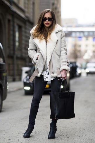 Comment porter: veste en peau de mouton retournée grise, chemisier à manches longues imprimé blanc et noir, jean skinny noir, bottines en cuir noires
