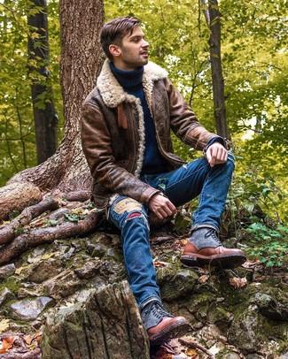 Comment porter: veste en peau de mouton retournée marron, pull à col roulé en laine bleu marine, jean déchiré bleu, bottes de loisirs en cuir marron
