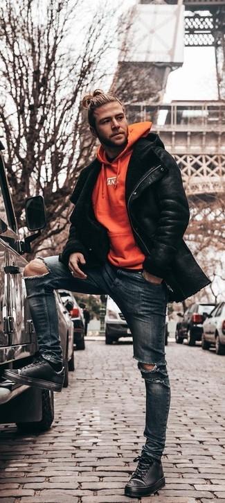 Comment porter: veste en peau de mouton retournée noire, sweat à capuche orange, jean skinny déchiré bleu marine, baskets basses en cuir noires