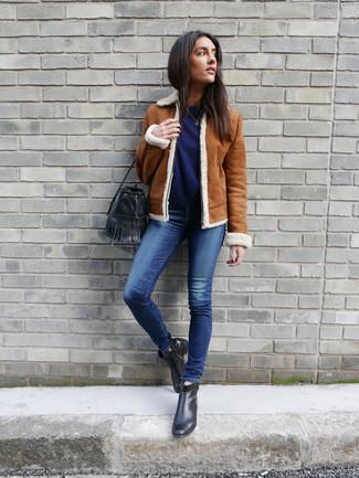 Comment porter: veste en peau de mouton retournée tabac, pull à col rond bleu marine, jean skinny bleu, bottines en cuir noires
