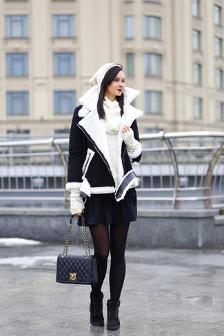 Comment porter: veste en peau de mouton retournée noire et blanche, pull à col rond blanc, jupe patineuse noire, bottines plates à lacets en daim noires