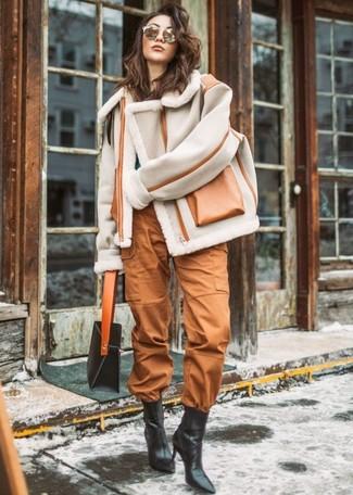 Comment porter: veste en peau de mouton retournée grise, pull à col rond bleu canard, pantalon cargo tabac, bottines en cuir noires