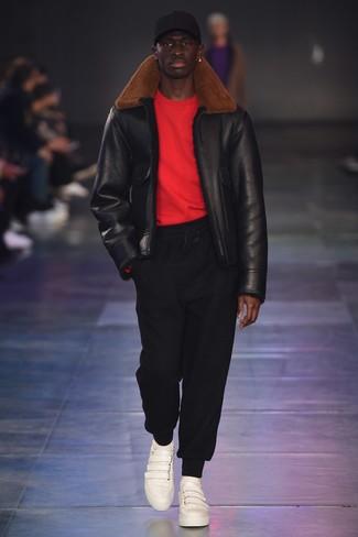 Comment porter: veste en peau de mouton retournée noire, pull à col rond rouge, pantalon de jogging noir, baskets basses en cuir blanches
