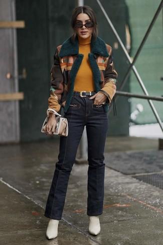 Comment porter: veste en peau de mouton retournée multicolore, pull à col roulé moutarde, jean flare bleu marine, bottines en cuir blanches