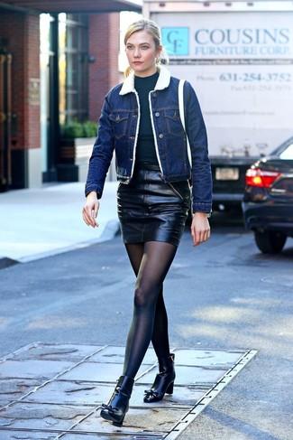Comment porter: veste en peau de mouton retournée en denim bleue, pull à col roulé noir, minijupe en cuir noire, bottines en cuir noires