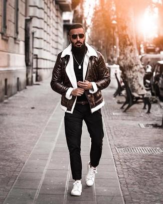 Comment porter: veste en peau de mouton retournée marron foncé, pull à col roulé noir, pantalon chino noir, baskets basses en cuir blanches
