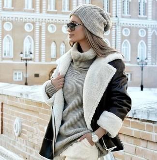 Comment porter: veste en peau de mouton retournée noire et blanche, pull à col roulé en tricot gris, pantalon de jogging beige, bonnet en tricot gris