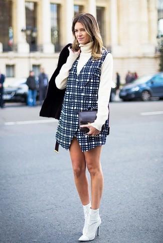 Comment porter: veste en peau de mouton retournée noire, pull à col roulé beige, robe chasuble à carreaux bleu marine, bottines en cuir découpées blanches