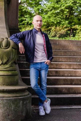 Comment porter un t-shirt à col rond beige: Harmonise un t-shirt à col rond beige avec un jean bleu pour un déjeuner le dimanche entre amis. Termine ce look avec une paire de des baskets basses en cuir blanches.