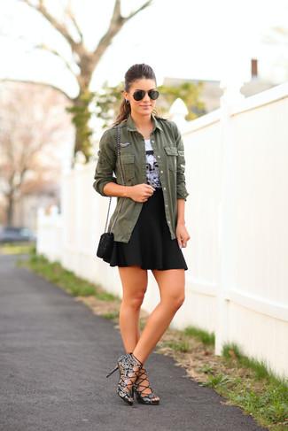 Comment porter: veste militaire olive, t-shirt à col rond imprimé blanc et noir, jupe patineuse noire, sandales à talons en cuir imprimées serpent grises