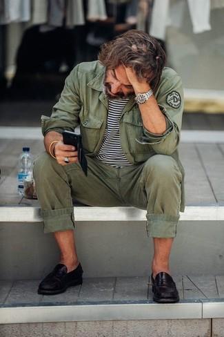 Comment porter: veste militaire olive, t-shirt à col rond à rayures horizontales blanc et noir, pantalon chino olive, slippers en cuir noirs
