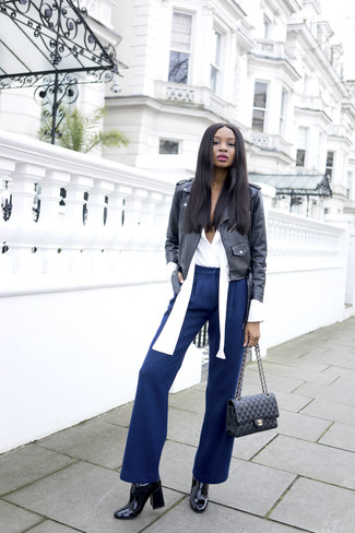 Comment porter: veste motard en cuir noire, chemisier à manches longues blanc, pantalon large bleu marine, bottines en cuir noires