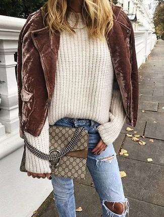 Comment porter: veste motard en daim marron, pull surdimensionné en tricot beige, jean déchiré bleu, sac bandoulière en cuir imprimé marron