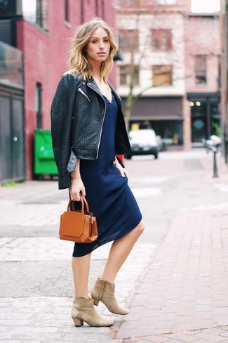 Comment porter: veste motard en cuir noire, robe nuisette bleu marine, bottines en daim beiges, pochette en cuir tabac