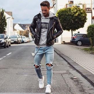 Comment porter: veste motard en cuir noire, sweat à capuche imprimé gris, jean déchiré bleu clair, baskets basses en cuir blanches