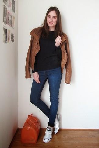 Comment porter: veste motard en cuir tabac, pull à col rond noir, jean skinny bleu marine, baskets basses blanches